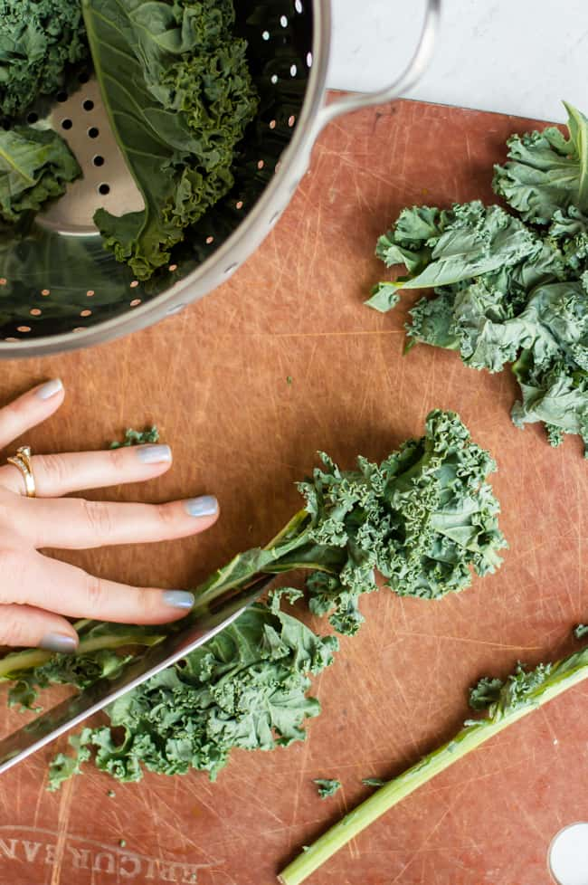 Kale leaves on a cutting board. Someone is slicing the hard rib out of the kale leaf.