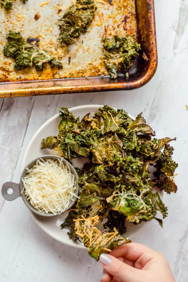 A bowl of kale chips on a plate with a bowl of Parmesan cheese. A hand is taking one of the chips and there is a baking tray with more chips next to the plate