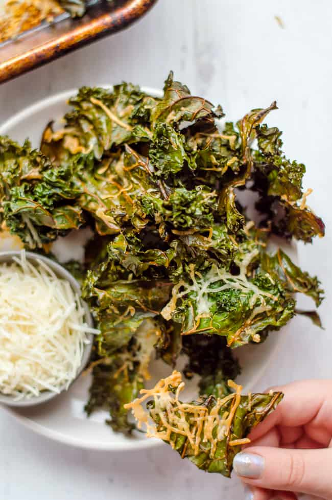 A bowl of kale chips on a plate with a bowl of Parmesan cheese. A hand is taking one of the chips.