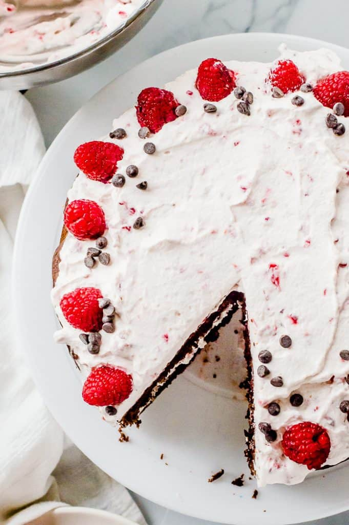 Chocolate beetroot cake with raspberry whipped cream on a cake plate. A slice has been cut from it and the cake is topped with fresh raspberries and chocolate chips