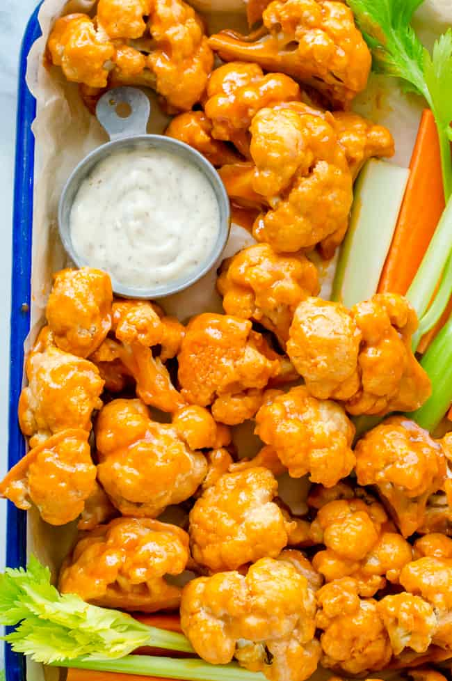 A tray of buffalo cauliflower wings with carrots and celery sticks and a bowl of ranch.