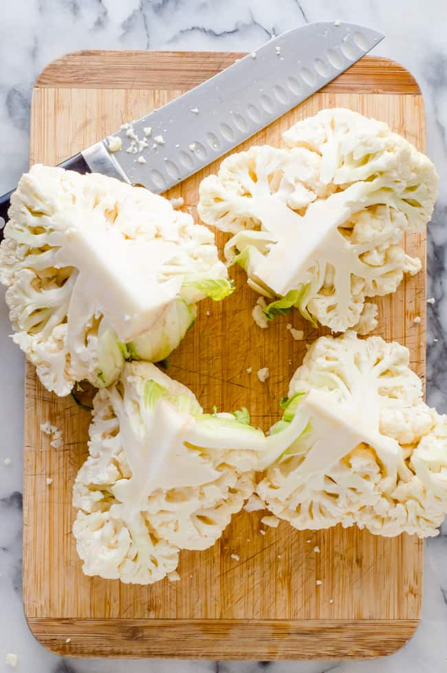 A cauliflower cut into quarters on a cutting board with a knife.