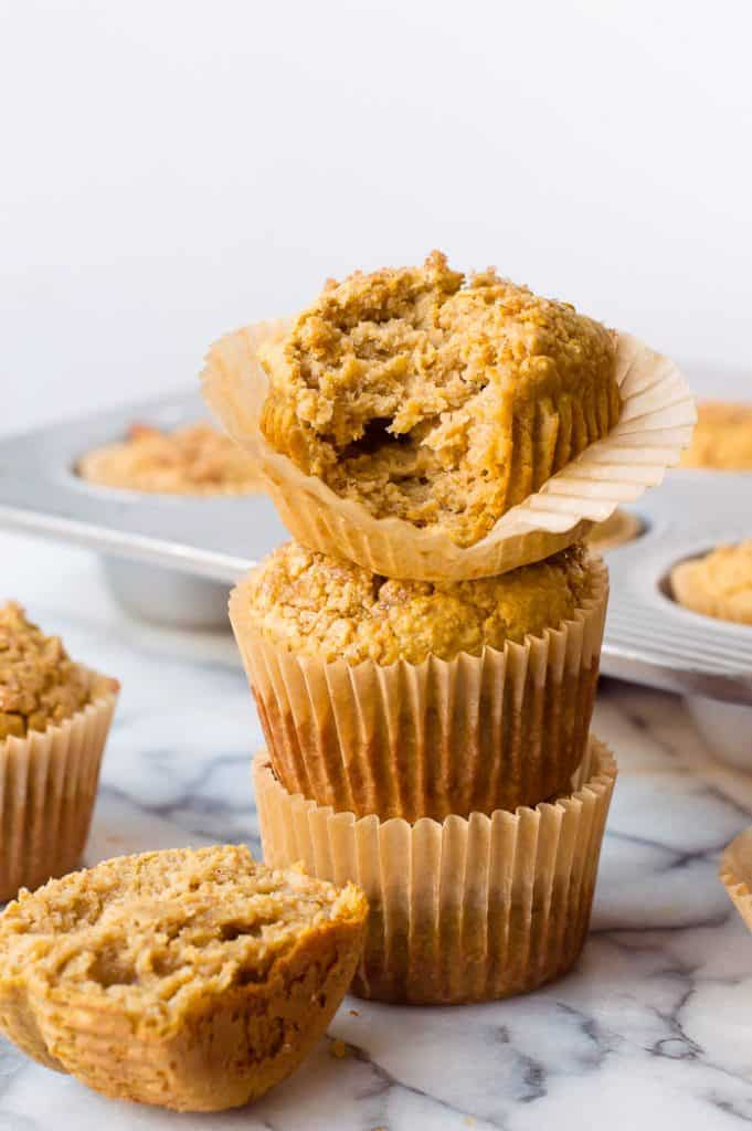 3 Butternut squash banana blender muffins stacked on one another. The top muffin has a bite taken out of it.
