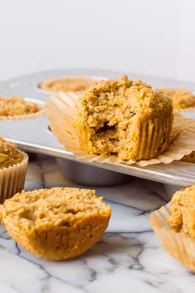 Butternut squash banana blender muffin with a bite out of it resting on the muffin tin. Other muffins are still in the tray and scattered around the table.