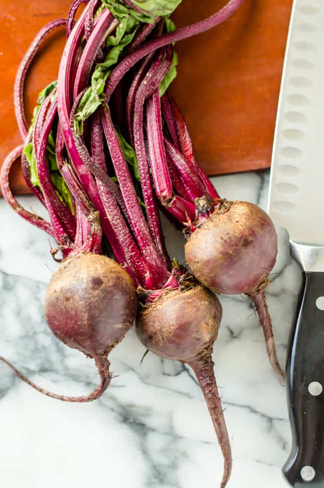 3 fresh beets on a cutting board with a knife