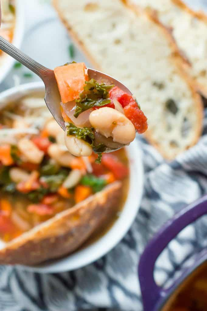 A spoon scooping up a bite of kale and white bean soup. The bowl of soup, bread and the pot of soup are blurred in the background