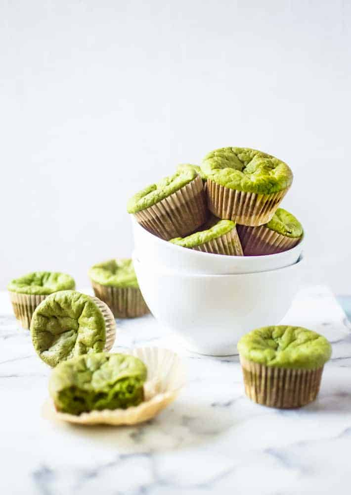 Paleo green smoothie muffins in a bowl. Several muffins are scattered around the bowl on the table