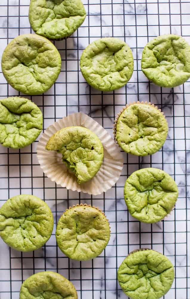 Paleo green smoothie muffins on a cooling rack. One muffin in the middle has a bite taken out of it.