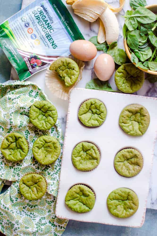 Paleo green smoothie muffins in a muffin tin, cooling on the table with muffin ingredients around it.