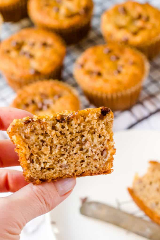 A hand holding half of a Paleo banana muffin. The rest of the batch is blurred in the background