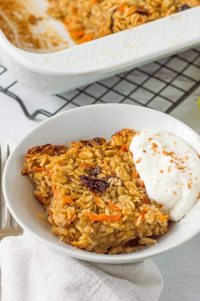 Carrot cake baked oatmeal in a bowl with yogurt on top. The tray of baked oatmeal is next to it.
