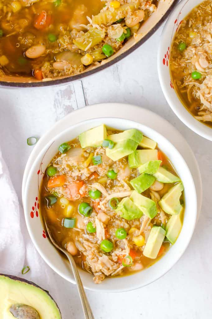 A bowl of chicken quinoa vegetable soup topped with avocado. Another bowl of soup and the pot of soup are next to it.