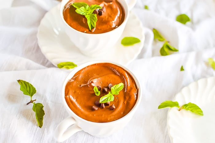 Mint chocolate avocado mousse in two tea cups with mint leaves scattered around them on the table