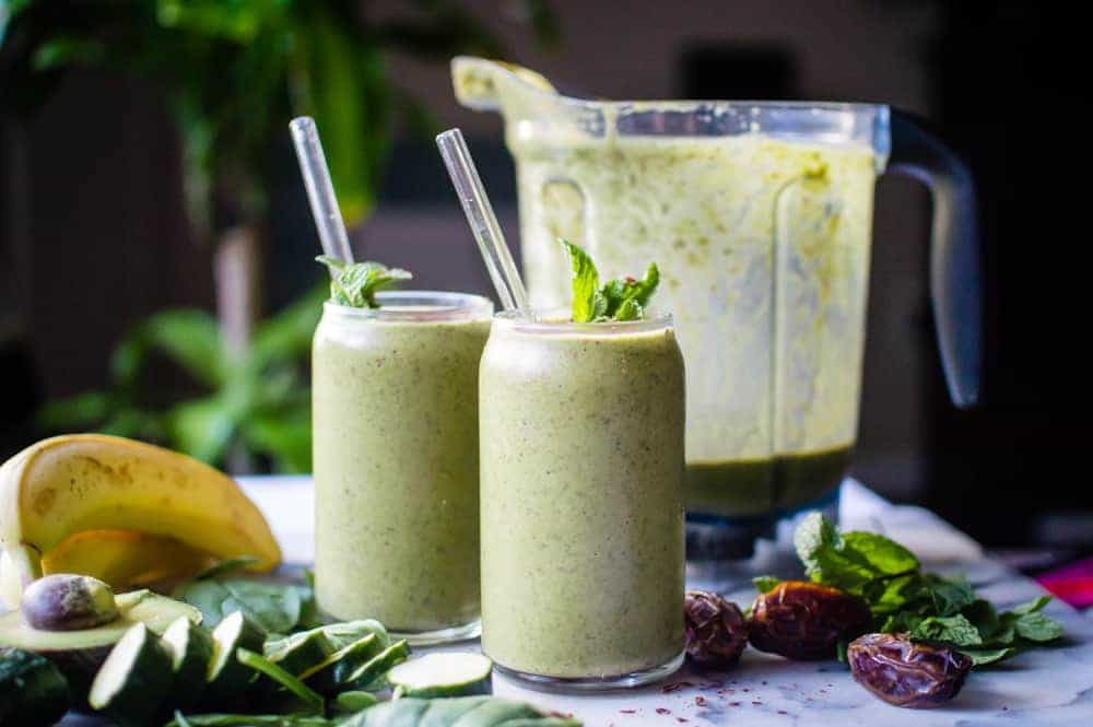 Healthy mint chocolate shake in two glasses with the blender and ingredients in the background