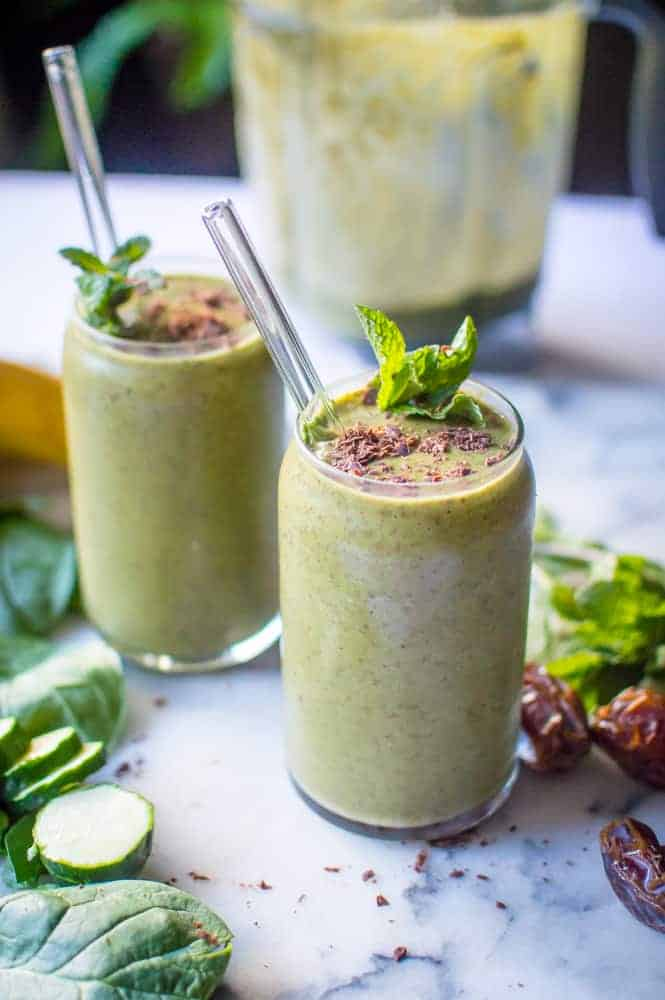 Healthy mint chocolate shake in two glasses, surrounded by ingredients.