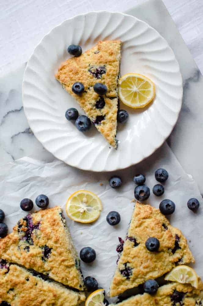 Blueberry Lemon Paleo scones on a white table with one scone pulled away from the batch. There are fresh blueberries and lemons scattered around.