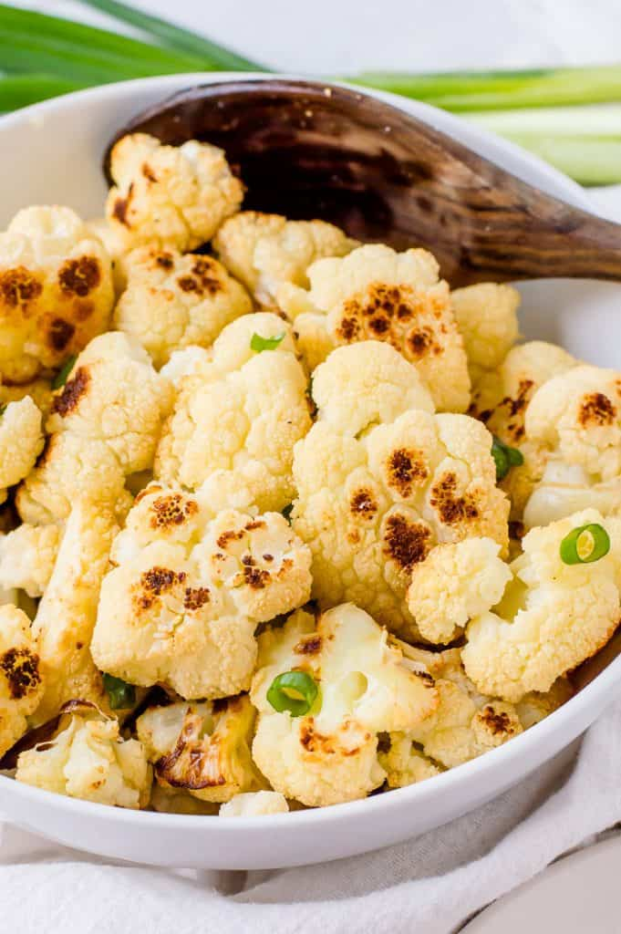 Roasted cauliflower in a bowl with a spoon.
