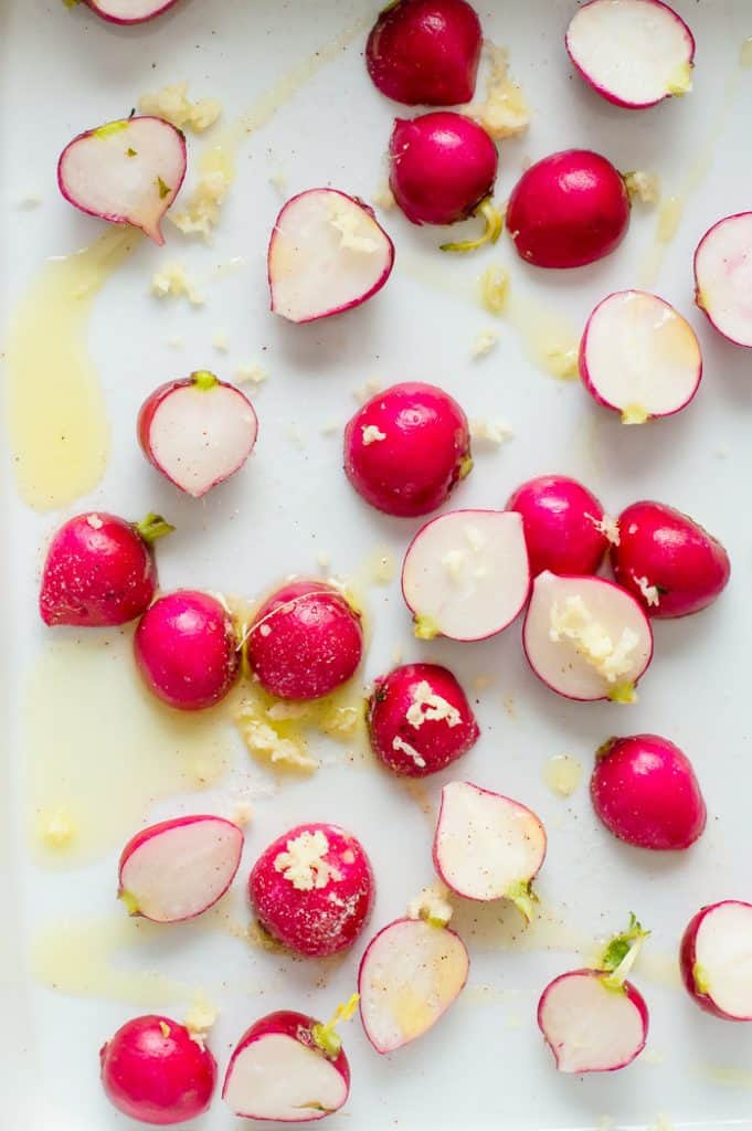 Raw radishes before roasting, drizzled with oil, salt and garlic in a baking dish.