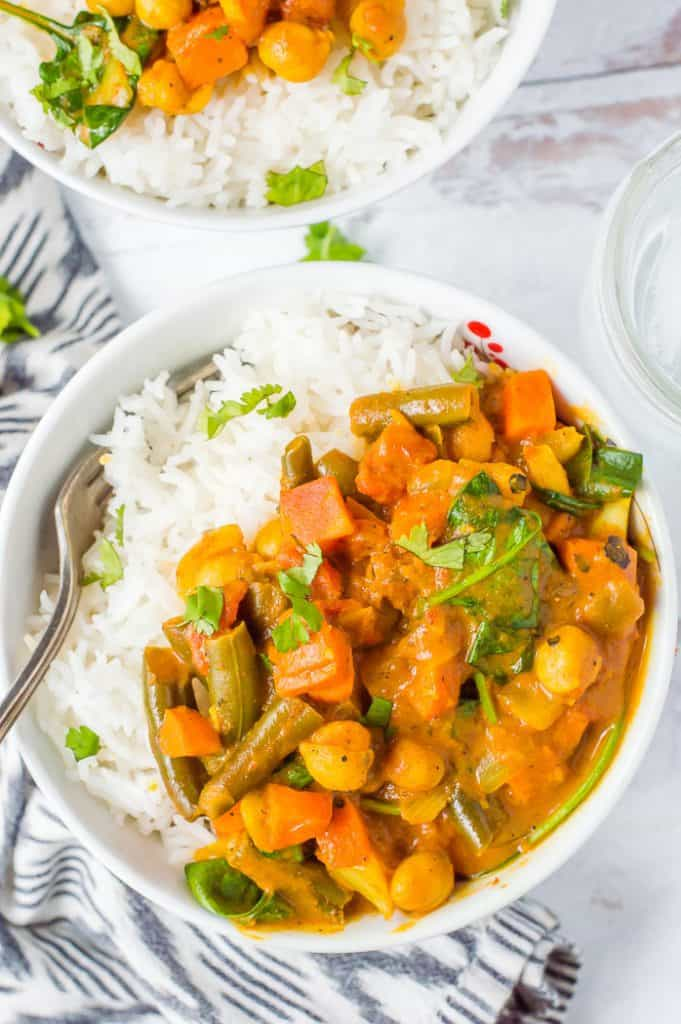 Two bowls of slow cooker chickpea vegetable curry with white rice. They are on top of a napkin and there is a fork in one bowl.