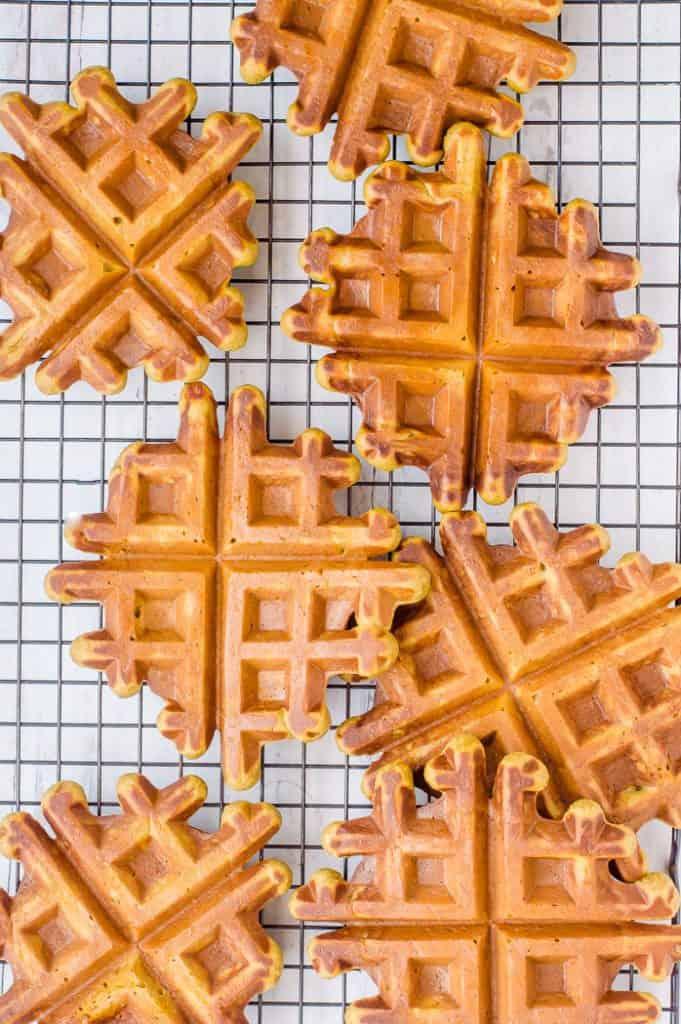A batch of superhero gluten free waffles on a cooling rack.