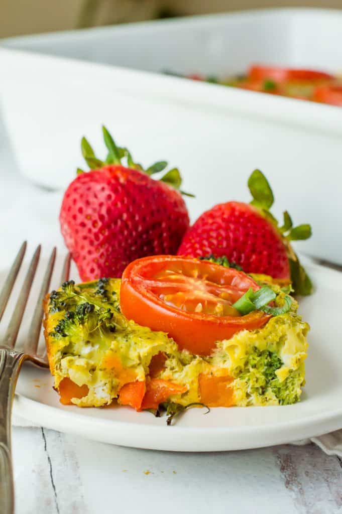 A slice of vegetarian breakfast casserole on a plate with a fork and strawberries.