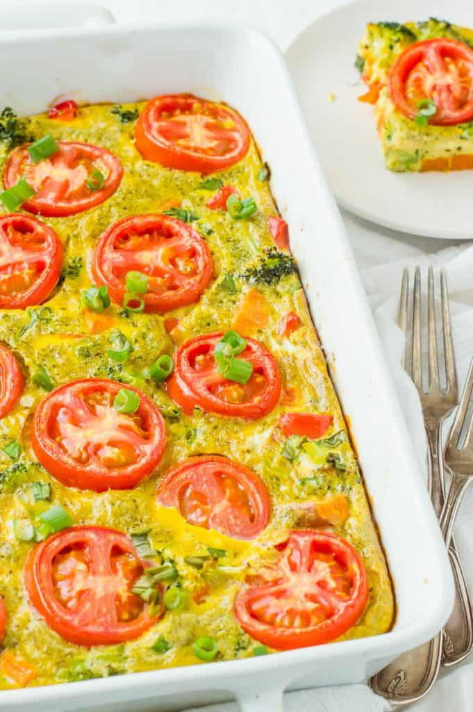 A dish of vegetarian breakfast casserole on the table with a slice on a plate in the background.
