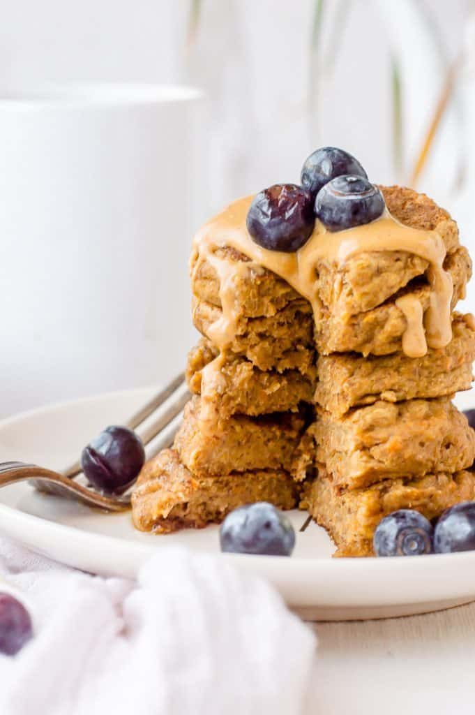 A stack of vegan banana protein pancakes with a bite sliced out of it. The stack has peanut butter dripping down in with blueberries on top and on the plate.