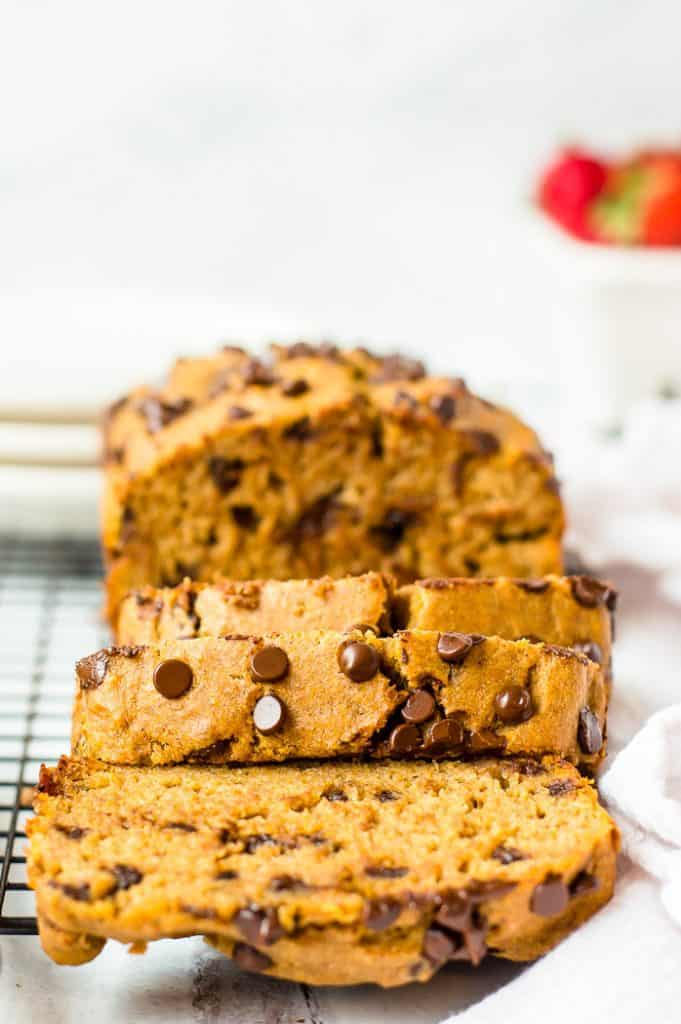 Sweet potato banana bread on a cooling rack with 3 slices cut from it.
