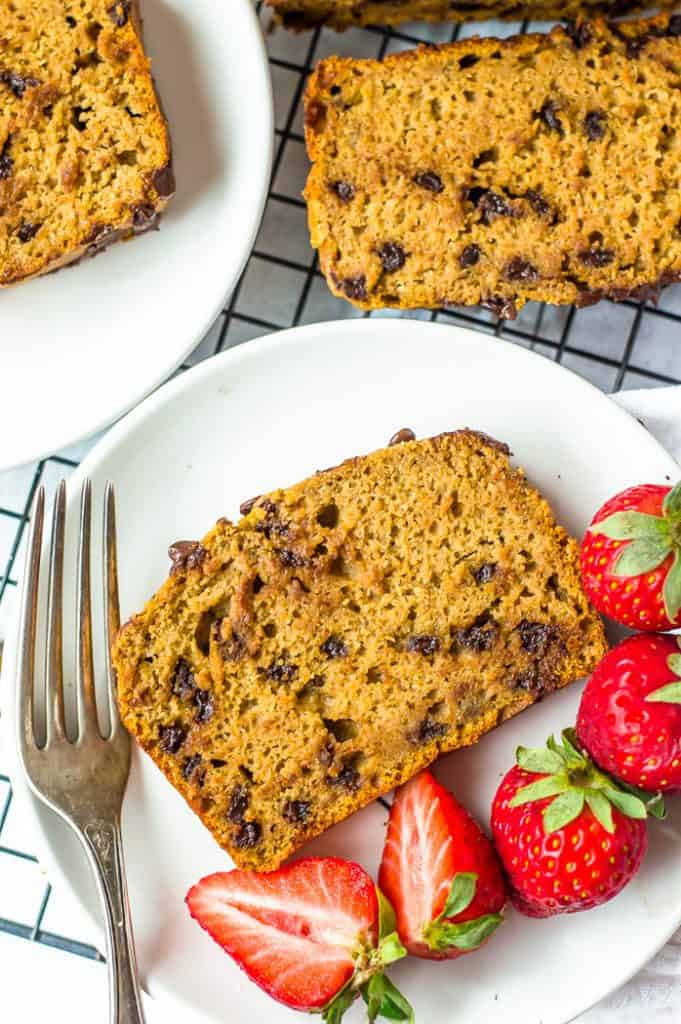 A slice of sweet potato banana bread on a white plate with a fork and strawberries.