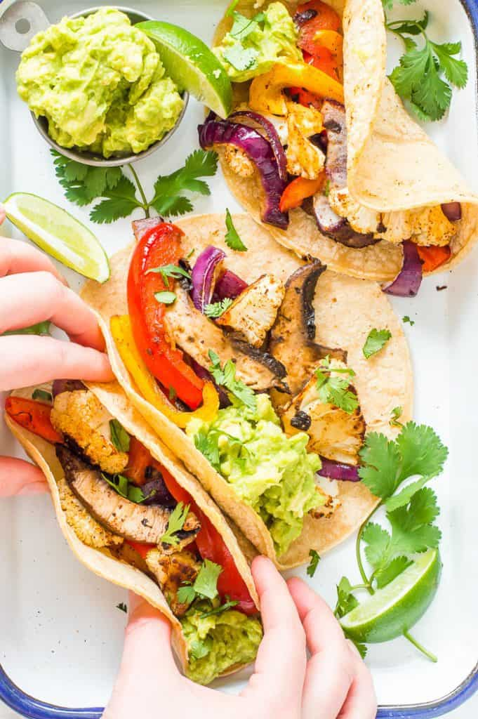 Sheet pan veggie fajitas on a tray with guacamole , limes and cilantro. A hand is taking one of the fajitas.