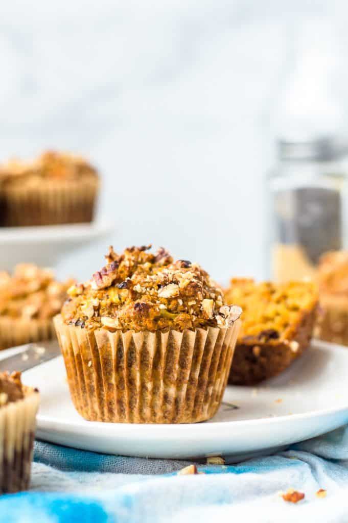A morning glory muffin on a plate. There are other muffins in the blurred background.