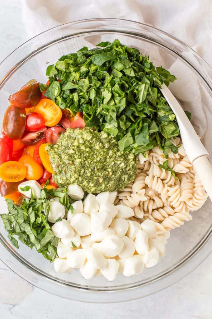 Ingredients for pesto veggie pasta salad in a bowl before mixing.