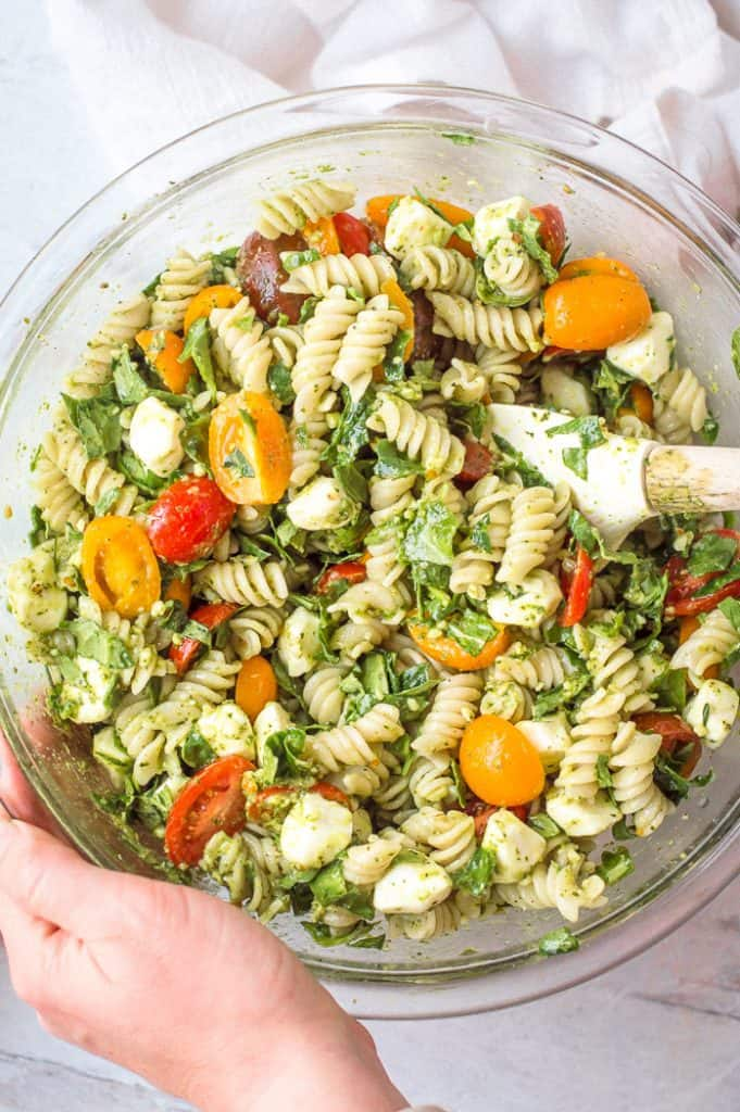 Pesto veggie pasta salad in a bowl after mixing.