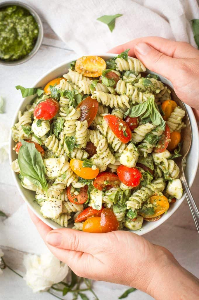 Pesto veggie pasta salad in a white bowl with a spoon. Hands are holding the bowl. There is a white napkin and cup of pesto next to it.