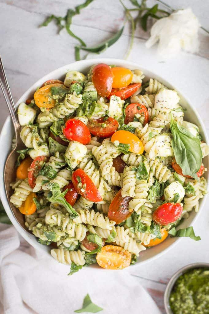 Pesto veggie pasta salad in a white bowl with a spoon. There is a white napkin and cup of pesto next to it.