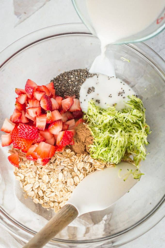 Ingredients for strawberry overnight oats in a bowl with a spoon and milk being poured into the bowl.