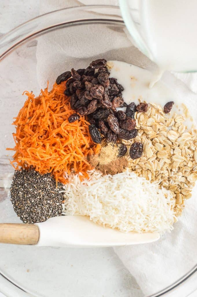 Ingredients for carrot cake overnight oats in a bowl before mixing.