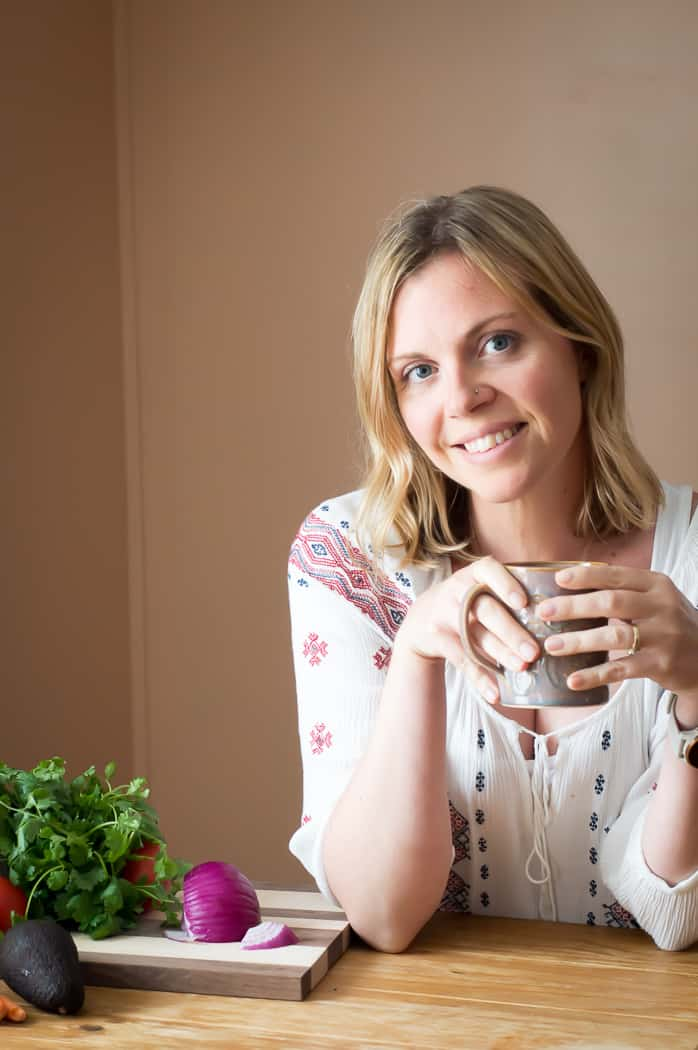 A blond woman holding a mug and smiling