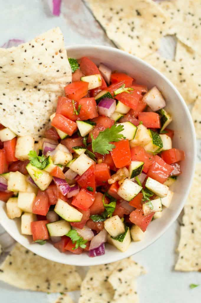 A bowl of zucchini salsa with a chip in it. There are more chips scattered around the bowl on the table.