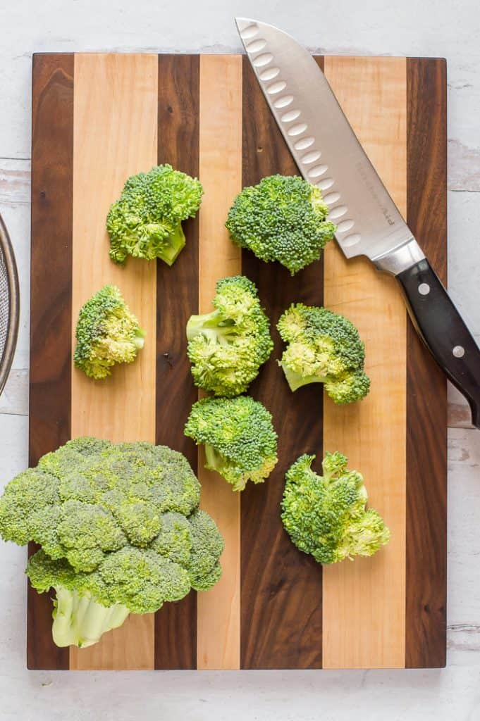 Broccoli florets on a cutting board with a chef's knife.