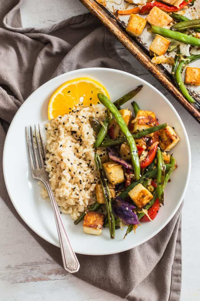Orange tofu and veggies in a bowl with rice and a fork.