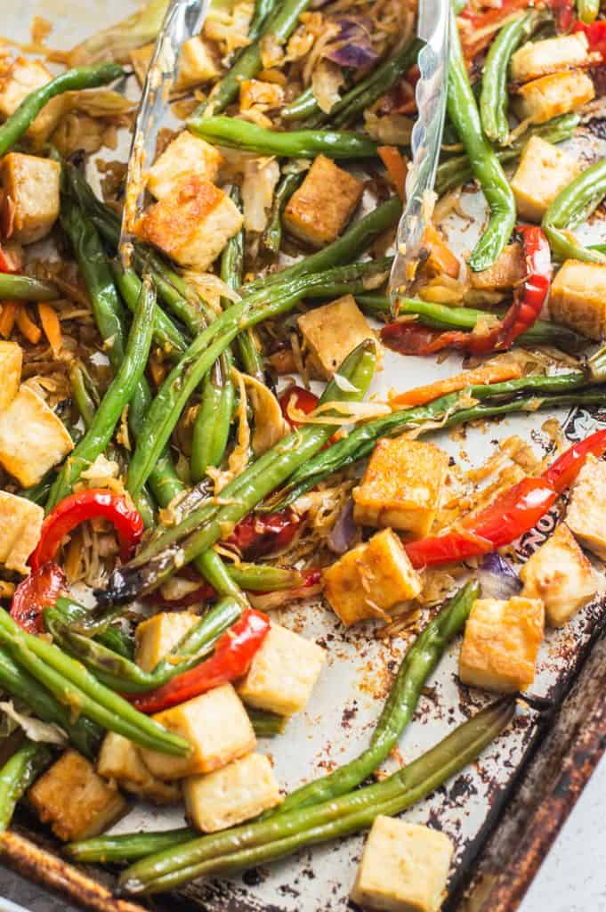 Veggie orange tofu sheet pan with tongs after it has come out of the oven.