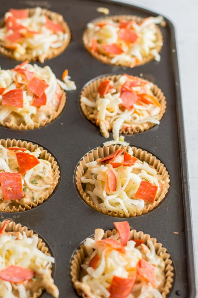 Veggie-loaded pizza muffins before cooking, sprinkled with cheese and pepperoni.