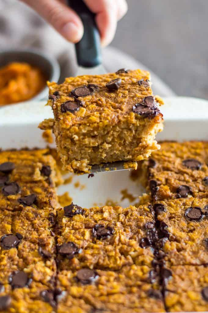 A slice of baked pumpkin oatmeal being lifted out of the tray with a spatula.