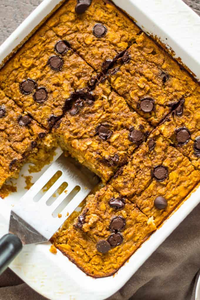 Baked pumpkin oatmeal in a tray with a slice missing.