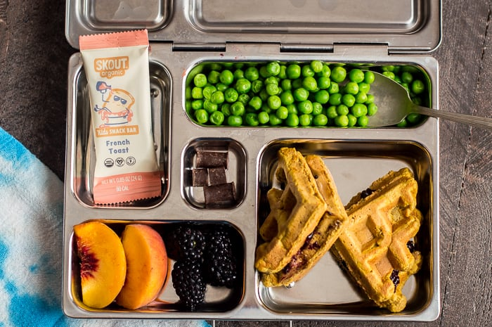 A metal bento box packed with peas, a waffle sandwich, blackberries, peaches, chocolate chunks and a Skout Organic bar.