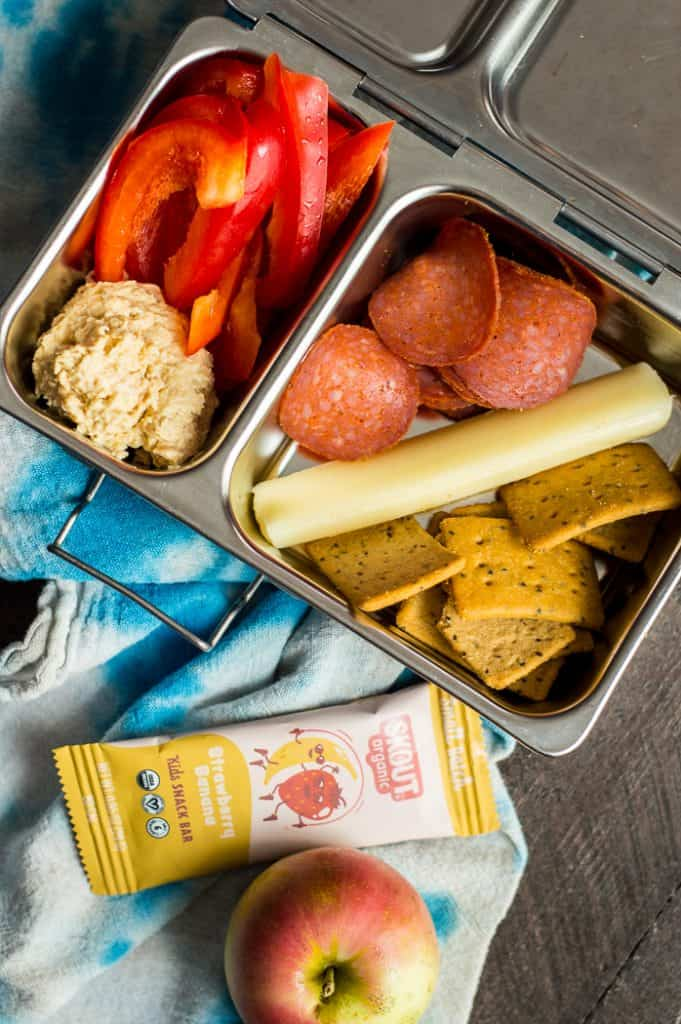 A metal bento box with two compartments. One compartment has bell peppers and hummus. The other has pepperoni, a cheese stick and crackers.