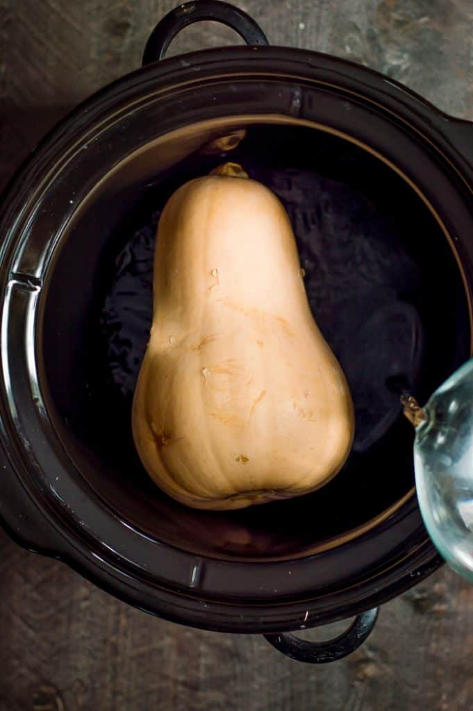 A whole butternut squash in a crockpot. Water is being poured into the crockpot.