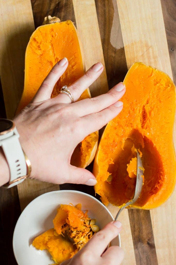 A cooked butternut squash on a cutting board cut in half. A person is scooping seeds out of it.