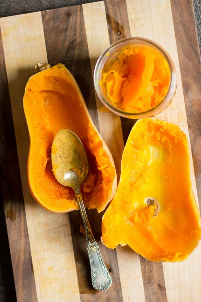 A cooked butternut squash on a cutting board with a spoon.